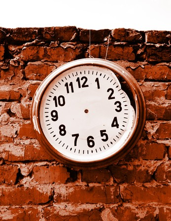 Broken clock without hands on the brick wall. Stock Photo