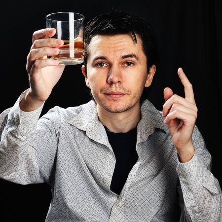 drank: Man wearing the white shirt with glass of whiskey in the hand. Black background. Stock Photo