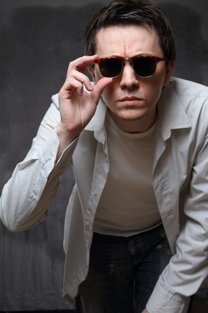 Man in the sunglasses posing on the grey background. Stock Photo - 8715199
