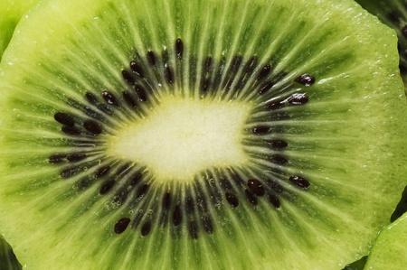 kiwi fruta: Sectores de Kiwi fresco en la placa verde.