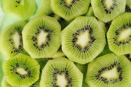 kiwi fruta: Rodajas de Kiwi fresco sobre la placa verde.  Foto de archivo