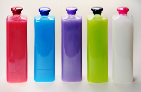 Bottles with color liquid soap on the white background. photo