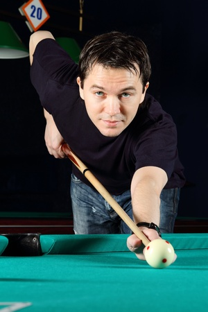 Man playing snooker in the dark club. photo