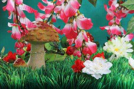 Artificial flowers and mushrooms on the plastic grass. photo