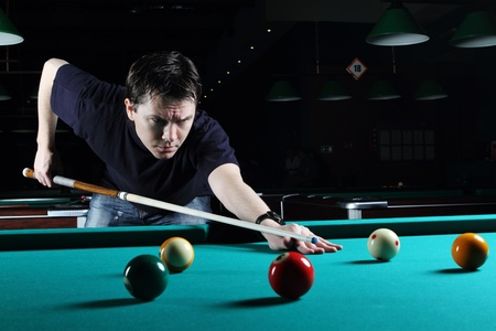 Man learning to play snooker in the dark club  Stock Photo