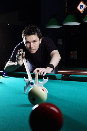 Man learning to play snooker in the dark club  photo