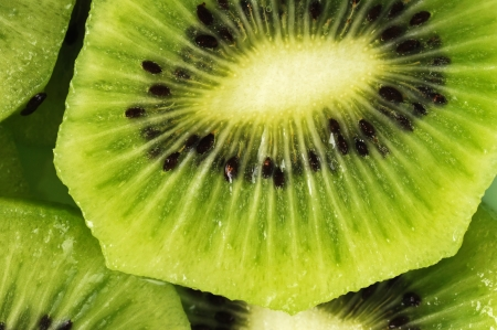 kiwi fruta: Rebanadas frescas de kiwi en la placa verde Close-up