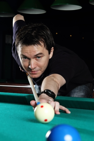 Man playing snooker in the dark club  photo