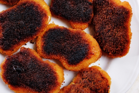 hen's: Slightly burnt chicken cutlets on the plate  Stock Photo