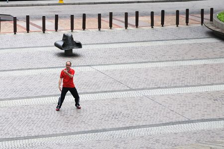 HONG KONG - JULY 18: Hongkonese man makes tai chi exercises on the street of Hong Kong. Hong Kong, China - July 18, 2011.
