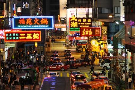 HONG KONG - JULY 18: People on the night street under neon lights.Hong Kong, China - July 18, 2011.