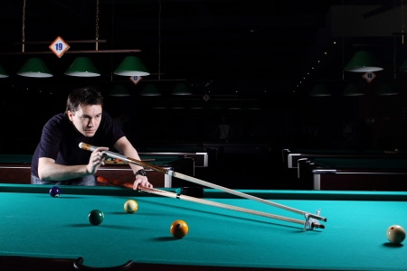 Homme jouant au billard dans le club de nuit Banque d'images