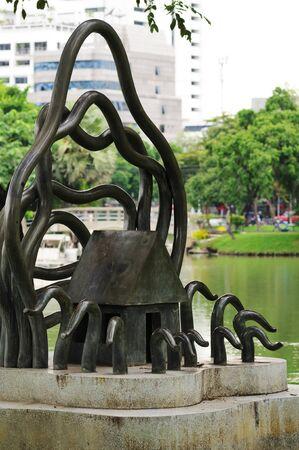 settles: BANGKOK - SEPTEMBER 5: Bronze sculpture in the Lumpini Park. Lumpini Park settles down in downtown of Bangkok. Bangkok, Thailand - September 5, 2011.
