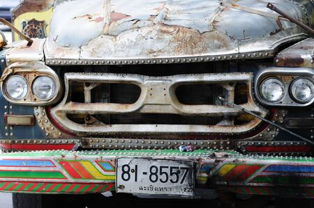 BANGKOK - SEPTEMBER 6: Thai truck decorated with painting. Front view. Old, rusty and scratched. In downtown of Bangkok. Bangkok, Thailand - September 6, 2011. Stock Photo - 16585527