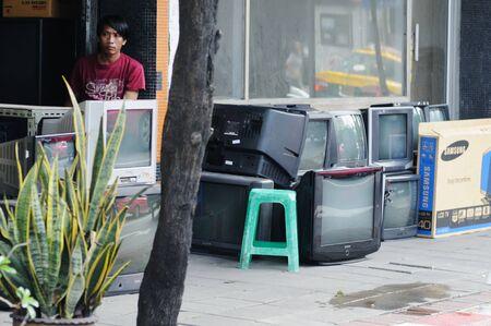 BANGKOK - SEPTEMBER 7: Seller in the small shop on the street waits a buyer for his goods - old TVs.. Bangkok, Thailand - September 7, 2011. Stock Photo - 16585504