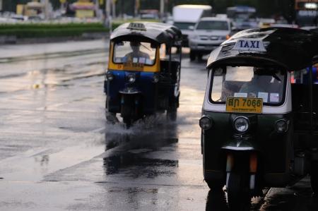 autorick: BANGKOK - SEPTEMBER 7: Two tuk-tuks on the street in downtown of Bangkok. Rainy weather. Bangkok, Thailand - September 7, 2011.