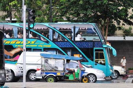 BANGKOK - SEPTEMBER 7: Double-decker bus and tuk-tuk are waiting green light on the crossroads in downtown of Bangkok. Rainy weather. Bangkok, Thailand - September 7, 2011. Stock Photo - 16585530