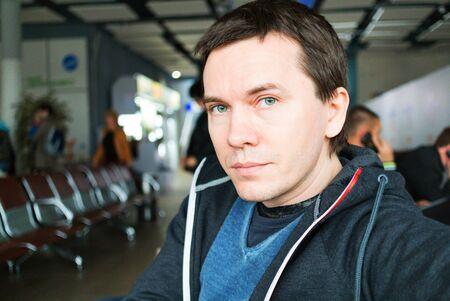 awaiting: Man awaiting departure in airport.