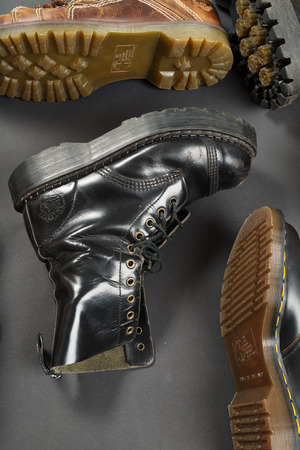 shiny black: LONDON, ENGLAND - FEBRUARY 4, 2016: Old-fashioned and worn boots on gray background. Classic Dr. Martens models and classic Grinders models. Editorial