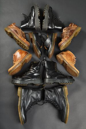 dr: LONDON, ENGLAND - FEBRUARY 4, 2016: Old-fashioned and worn boots on gray background. Classic Dr. Martens models and classic Grinders models. Editorial