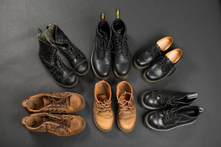 LONDON, ENGLAND - FEBRUARY 4, 2016: Old-fashioned and worn boots on gray background. Classic Dr. Martens models and classic Grinders models. Editöryel