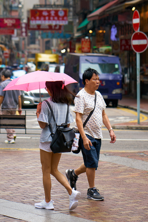 HONG KONG - SEPTEMBER 2, 2017: People walk on the streets of Hong Kong Island when its raining.