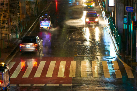 BANGKOK, THAILAND - July 7, 2017: Road traffic in Bangkok downtown. Noisy and colorful vehicles on the crowded streets. Rainy weather.