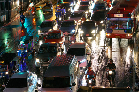 BANGKOK, THAILAND - July 7, 2017: Road traffic in Bangkok downtown. Noisy and colorful vehicles on the crowded streets. Rainy weather. 写真素材 - 103203218