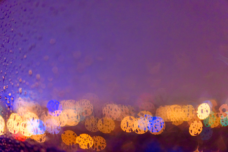 Abstract out of focus background. View through the window glass in rainy weather.