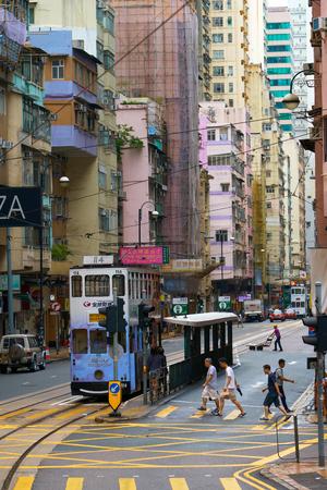 HONG KONG - September 4, 2017: Pedestrians crossing road in front of double decker tram stop. Street scene in Hong Kong.