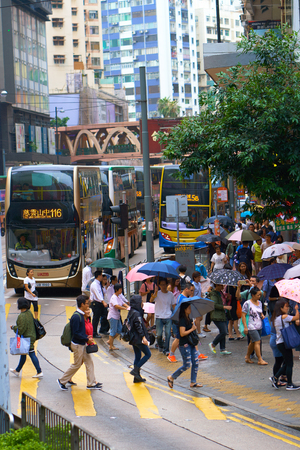 HONG KONG - September 4, 2017: Double decker buses and people with umbrellas crossing street. City hustle and bustle. Editöryel