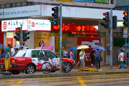 HONG KONG - September 4, 2017: Red taxi cab stops on red traffic light, while pedestrians with umbrellas crossing road. Street scene in Hong Kong in rainy weather. Editorial
