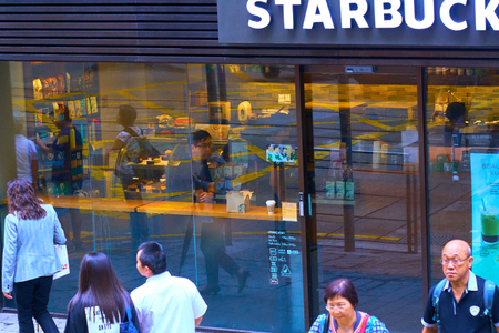 HONG KONG - September 4, 2017: Hustle and bustle of busy city streets reflecting in glass window of Starbucks coffeehouse. Scene of daily life in Hong Kong. Illustrative editorial. Editöryel