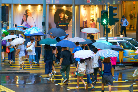 HONG KONG - September 4, 2017: Crowd of people with umbrellas crossing wet road. City hustle and bustle. Hong Kong streets in rainy weather. Editöryel