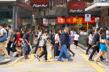 HONG KONG - September 5, 2017: Street scene of people crossing narrow street in downtown of densely populated asian metropolis. City hustle and bustle.