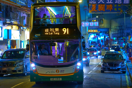 HONG KONG - September 5, 2017: Asian metropolis traffic scene with double decker bus during evening rush hours. Vibrant colors of night city.