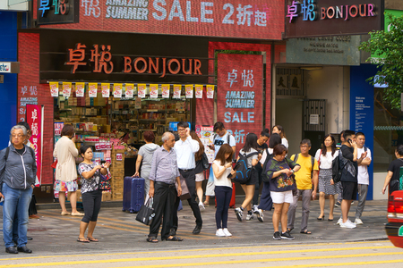 HONG KONG - September 5, 2017: People standing on sidewalk and waiting for crossing road in front of Bonjour cosmetic chain store. Street scene in Hong Kong. Editöryel