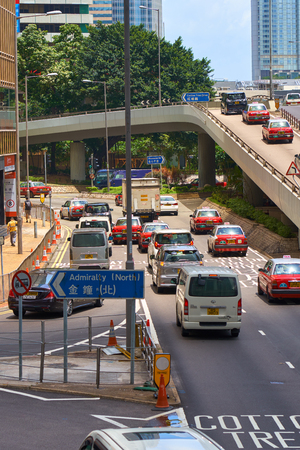 HONG KONG - July 4, 2018: Road traffic scene with red taxi cars on multi-level junction. Big city hustle and bustle. Editöryel