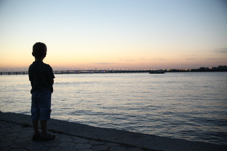 The little boy on the banks of the river watching the sunset Stok Fotoğraf