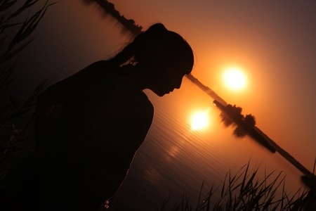 A girl stands on the shore of the lake at sunset. Stok Fotoğraf - 41048813
