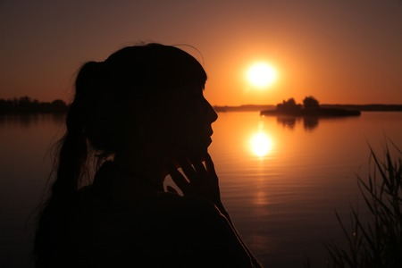 A girl stands on the shore of the lake at sunset.