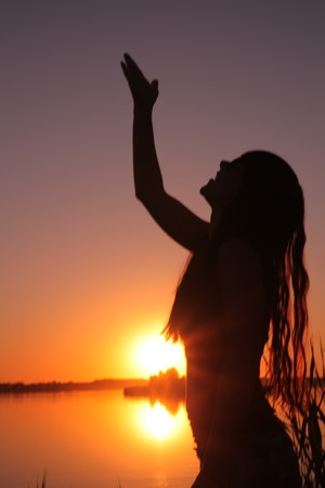 A girl stands on the shore of the lake at sunset. Stok Fotoğraf - 41048825