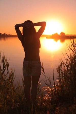 garish: A girl stands on the shore of the lake at sunset.