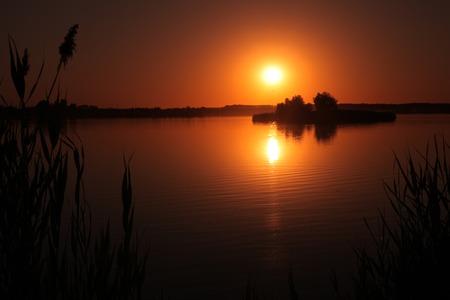 Sunset on the lake. Romantic beautiful evening on the nature Stok Fotoğraf