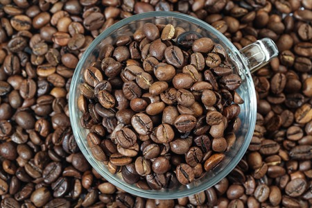 Glass Cup With Roasted Coffee Beans on The Table. Close-up