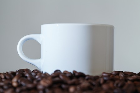 White Cup on The Table With Beans Roasted Coffee. Close-up Stok Fotoğraf