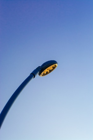 Led street lighting pole on blue sky background with sunset