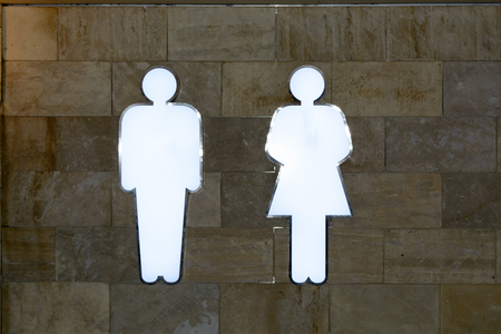 public building: A light guide in the WS - shape men and women, glowing white neon on the wall in a public building