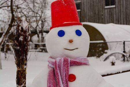 stovepipe: homemade Snowman stands in winter landscape smiling at the camera in the yard