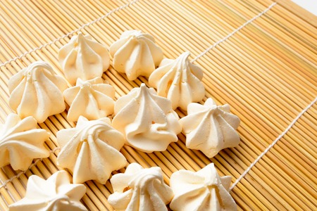 tasty of meringues on wooden rug background
